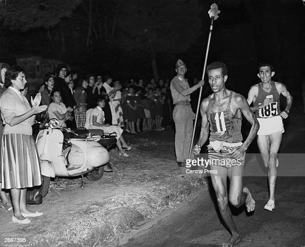 Abebe Bikila of Ethiopia running barefoot draws away from Abdesselem Rhadi of Morocco near the finish of the marathon at the 1960 Rome Olympics He...