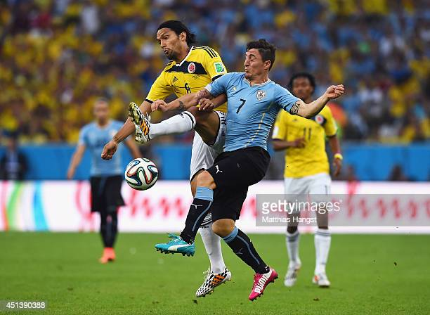 Abel Aguilar of Colombia and Cristian Rodriguez of Uruguay compete for the ball during the 2014 FIFA World Cup Brazil round of 16 match between...