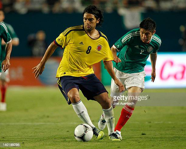 Abel Aguilar of Colombia has his jersey pulled by Oribe Peralta of Mexico as he carries the ball up field on February 29 2012 during an International...