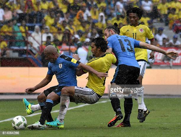 Abel Aguilar of Colombia vies for the ball with Gaston Silva and Carlos Sanchez of Uruguay during a match between Colombia and Uruguay as part of...