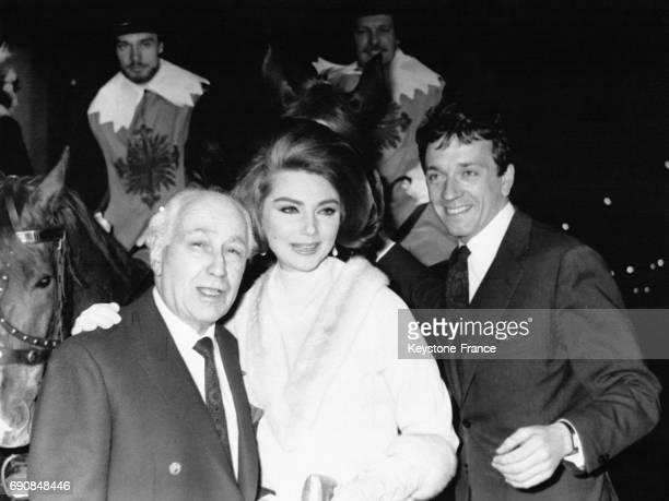 Abel Gance Sylva Koscina et JeanPierre Cassel devant des Mousquetaires du Roy à cheval devant le cinéma Colisée pour la projection de leur film...