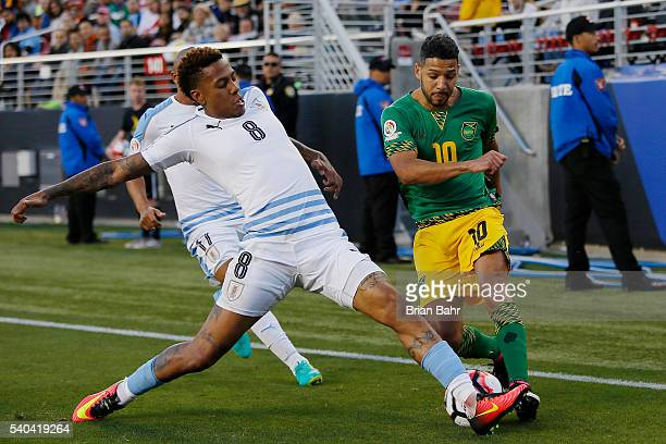 Abel Hernandez of Uruguay blocks a kick by Joel McAnuff of Jamaica during a group C match at Levi's Stadium as part of Copa America Centenario US...
