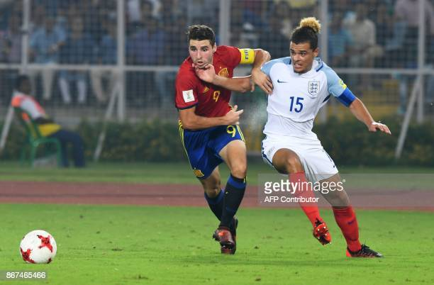 Abel Ruiz of Spain fights for the ball with Joel Latibeaudiere of England during their final FIFA U17 World Cup football match at the Vivekananda...