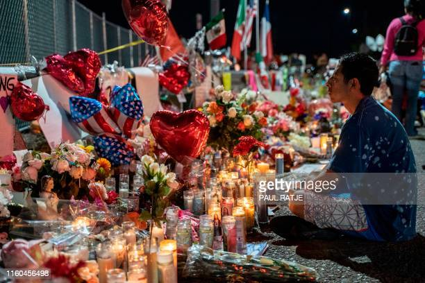 TOPSHOT Abel Valenzuela local of El Paso meditates in front of the makeshift memorial for shooting victims at the Cielo Vista Mall Walmart in El Paso...