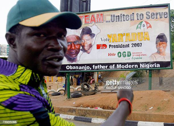 A supporter of People's Democratic Party the party of outgoing president Olusegun Obasanjo points to a party poster 20 April 2007 in Abeocuta ahead...