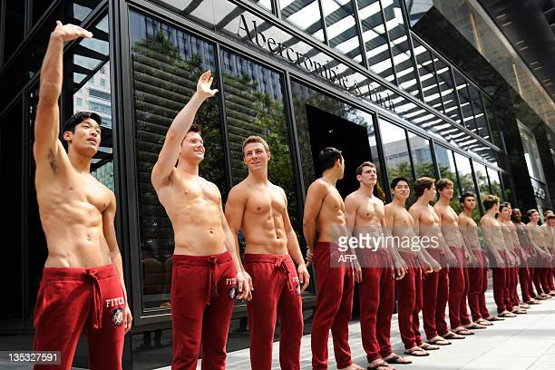 Abercrombie & Fitch models beckon the public to take pictures with them outside the A&F store in Knightsbridge, a Singapore shopping mall on December...