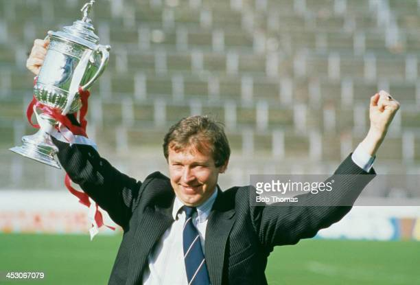 Aberdeen FC manager Alex Ferguson raises the trophy after his team won the Scottish Cup final against Rangers FC at Hampden Park Glasgow 22nd May...