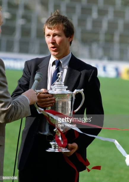 Aberdeen manager Alex Ferguson holds the Cup while being interviewed for television after his team's victory over Glasgow Rangers in the Scottish FA...