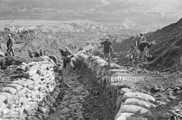 Emergency services and miners up on the hillside where the mud slid from Seen here with sandbags built up as a wall to stem the slow of any further...