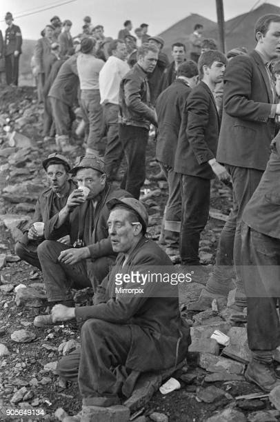 Miners take a short well earned break for a sit downa hot drink cigarette and to gather their thoughts as the rescue effort carries on behind them...