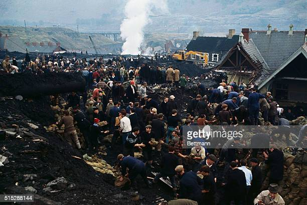 Hundreds of rescue workers dig into a huge pile of rubble after thousands of tons of coal pit waste slid down onto this village in southern Wales...