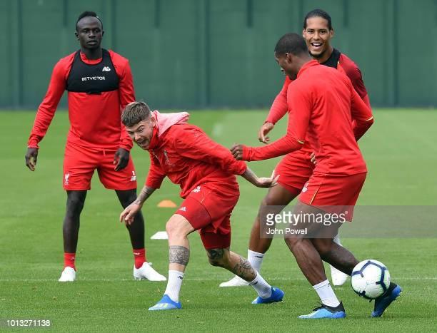 Aberto Moreno with Virgil van DijkSadio Mane and Georginio Wijnaldum of Liverpool during a training session at Melwood Training Ground on August 8...
