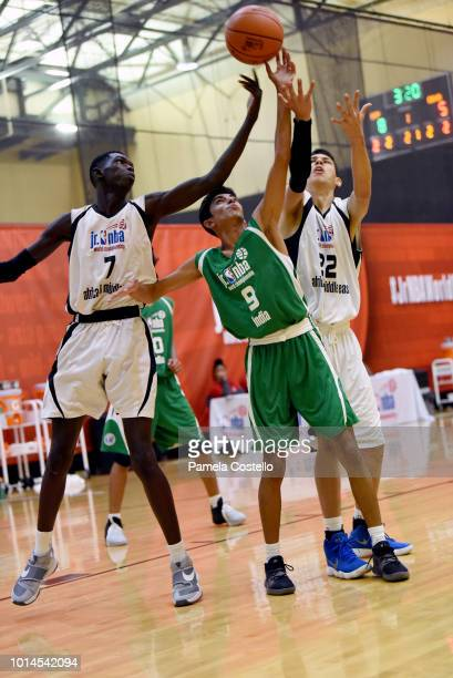 Abhishek Singh of the India Boys goes up for a rebound against Marouf Moumine and Mohamed Khalil Khemiri of the Africa and Middle East Boys during...