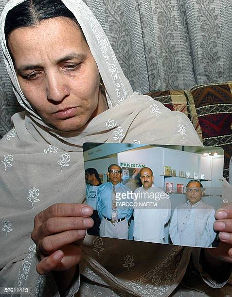 Abida Bibi the wife of Pakistani national Malik Muhammad Javed shows a family photo of her husband in Islamabad 10 April 2005 Javed a nondiplomatic...