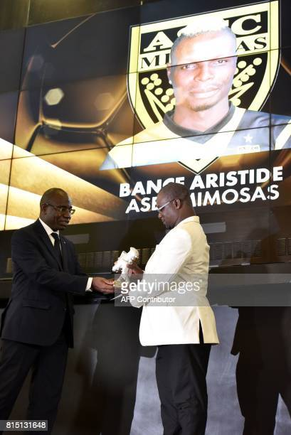 Abidhan's secretary general Djoman Francis receives the trophy of the Ivorian Ligue 1 best scorer for football player Aristide Bance during a...