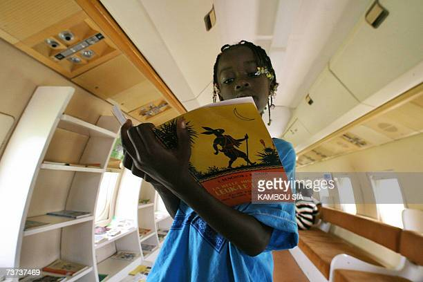 A pupils reads a book during a visit in the Fokker 27 named 'Oiseau Livre' 28 March 2007 in Abidjan the first plane of the first Ivorian President...