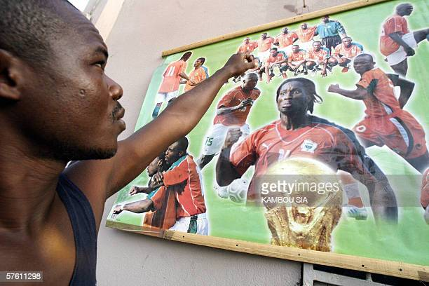 A supporter of the Ivorian selection shows 15 May 2006 in Koumassi a popular district of Abidjan a wall of his home decorated with pictures of the...
