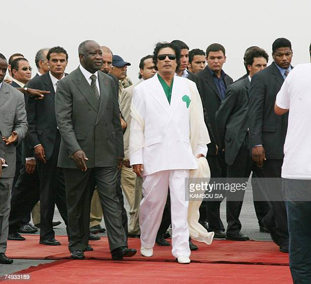 Libyan leader Moamer Kadhafi is accompanied by Ivory Coast President Laurent Gbagbo and bodyguards upon his arrival at Felix Houphouet Boigny airport...