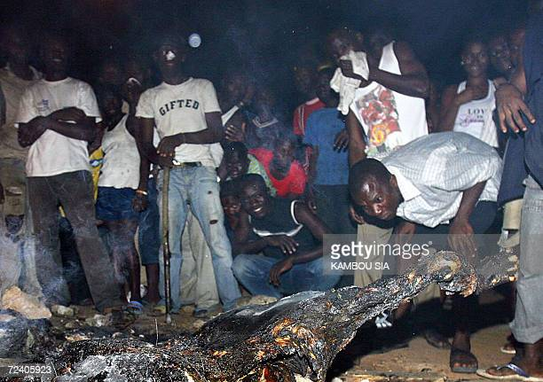 Local residents look at the burnt bodies of two propresidential militia members accused of racketeering and abuse and who were burned alive during a...