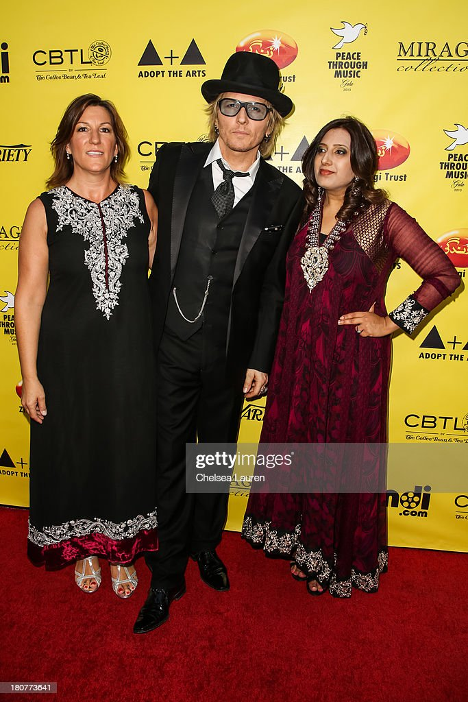 Abigail Berman, musician Matt Sorum and Sadia Ashraf arrive at Adopt the Arts' Peace Through Music celebrity gala at Loews Hollywood Hotel on September 15, 2013 in Hollywood, California.