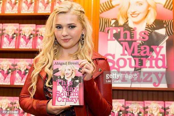 "Abigail Breslin shows a copy of her new book ""This May Sound Crazy"" during a book signing on October 4, 2015 in Metairie, Louisiana."