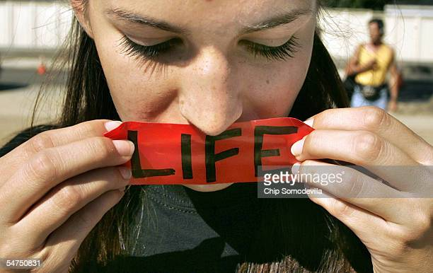 Abigail Brown Phoenix Arizona puts a LIFE sticker over her mouth while praying in front of the Supreme Court building September 5 2005 in Washington...