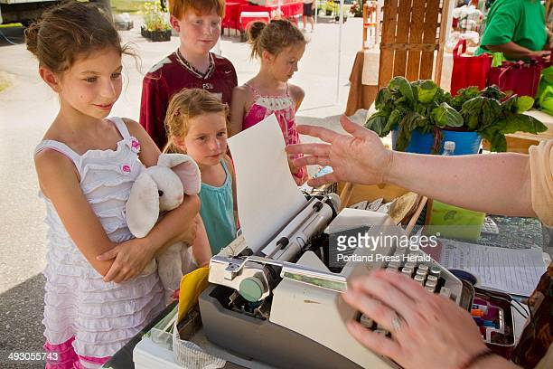 Abigail Kline 9 of Destin Fla at left watches as Holly Morrison an organic farmer from Pownal loads up the typewriter to create a poem commissioned...
