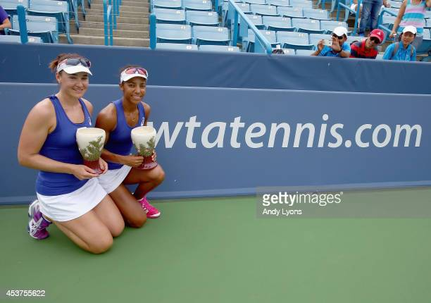Abigail Spears and Raquel KopsJones hold the winner's trophies after winning the women's doubles during the finals of the Western Southern Open on...