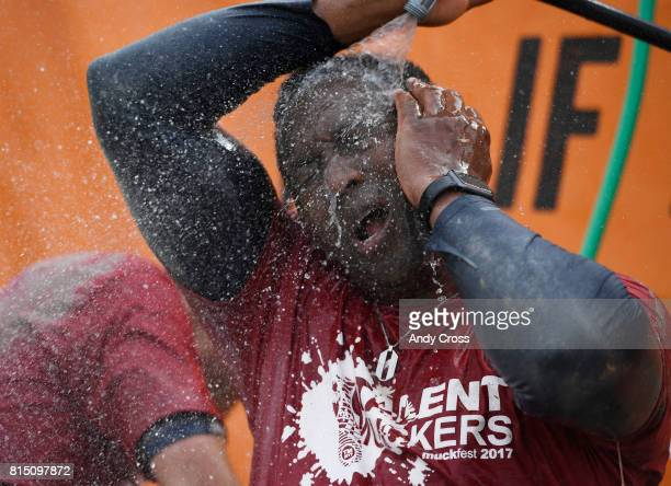 Abiola Okapo of the Great West Financial team cleans off the mud from his face after tackling MuckFest MS Denver course July 15 2017 at Salisbury...