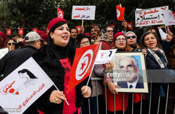 Abir Moussi president of Tunisia's Free Destourian Party shouts slogans as another colleague holds up a portrait of late president Habib Bourguiba...
