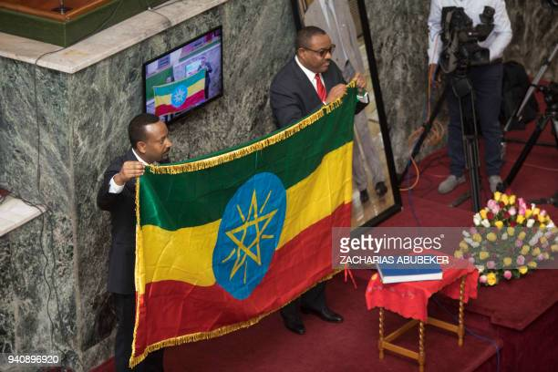 Abiy Ahmed newly elected Prime Minister of Ethiopia holds an Ethiopian flag with his predecessor Hailemariam Dessalegn at the house of Parliament in...
