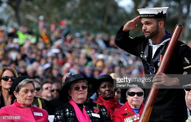 Able Seaman Boatswain's Mate Alan Patterson of NUSHIP Adelaide and member of the Gunggandji people salutes after playing the didgeridoo during the...
