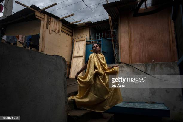 Abnaim Malud a gay resident of Marawi tries on a curtain to serve as a gown on October 20 2017 in Saguiaran southern Philippines Abnaim now lives as...