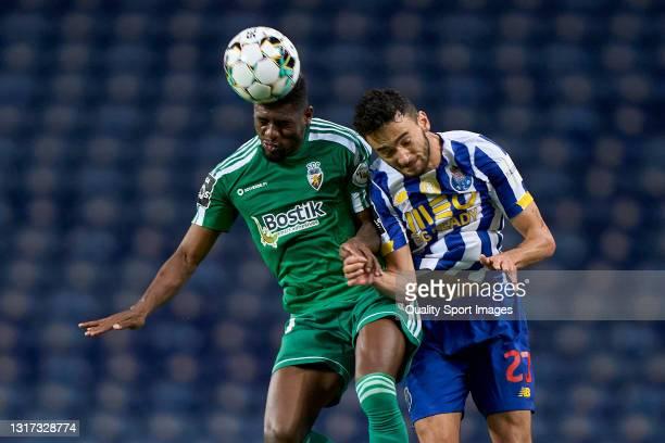 Abner Felipe Souza de Almeida of SC Farense competes for the ball with Joao Mario of FC Porto during the Liga NOS match between FC Porto and SC...