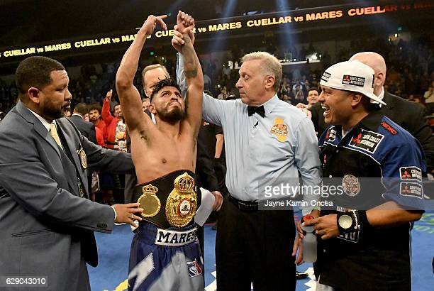 Abner Mares holds up his arms in the ring as his trainer Robert Garcia looks on after defeating Jesus Cuellar in the WBA Featherweight Championship...