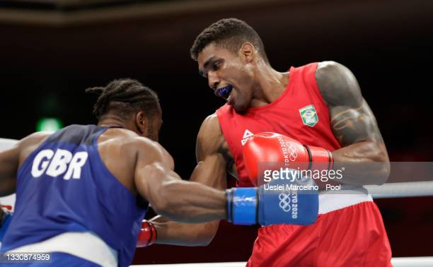 Abner Teixeira of Brazil exchanges punches with Cheavon Clarke of Great Britain during the Men's Heavy on day four of the Tokyo 2020 Olympic Games at...