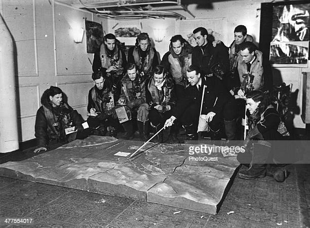 Aboard a British aircraft carrier Commander STC Harrison of the ship's air staff briefs crews with the aid of a relief map of the target area April...