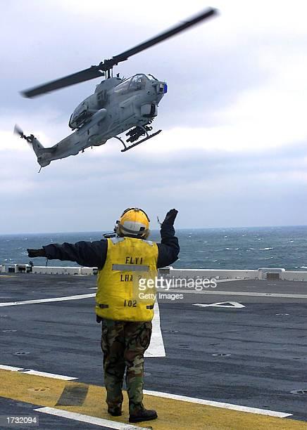 Aboard the amphibious assault ship USS Saipan Aviation Boatswains Mate 3rd Class Jennifer Rohrbaugh signals to an AH1W Super Cobra helicopter...