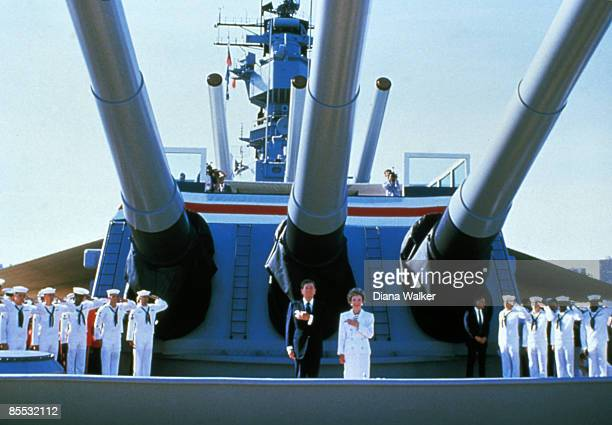 Aboard the battleship USs Iowa American President Ronald Reagan and his wife First Lady Nancy Reagan hold their hands over their hearts while...