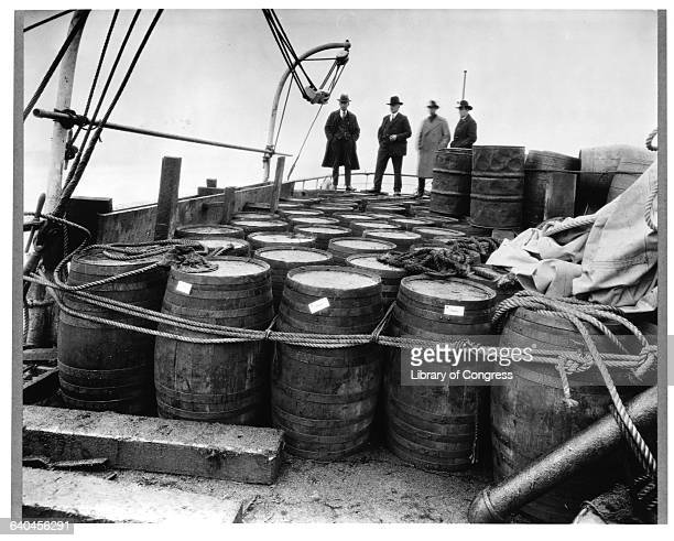 Aboard the Coast Guard Cutter USS Seneca Prohibition agents examine barrels of alcohol confiscated from a 'rum runner' boat
