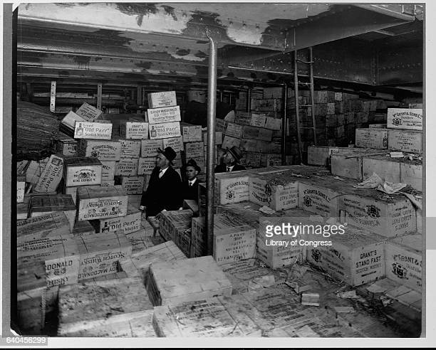 Aboard the Coast Guard Cutter USS Seneca Prohibition agents stand amidst cases of scotch whiskey confiscated from a 'rum runner' boat