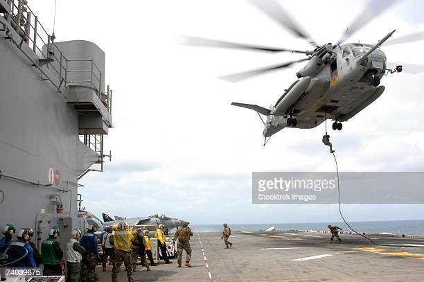 Aboard the USS Essex Marines and sailors fast-rope from a CH-53E Super Stallion helicopter of Marine Medium Helicopter Squadron 265 (Reinforced) onto the flight deck here November 15, during fast-rope training.