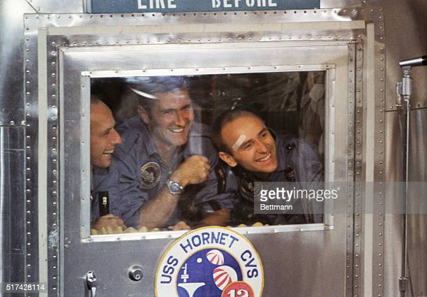Aboard The USS Hornet Safely aboard the carrier Hornet Apollo 12 astronauts gin from the window of their Mobile Quarantine Facility Left to right...
