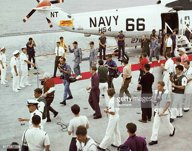 Aboard the USS Iwo Jima Apollo 13 astronauts stride on a red carpet aboard he carrier Iwo Jima after their splashdown in the Pacific Wearing blue...