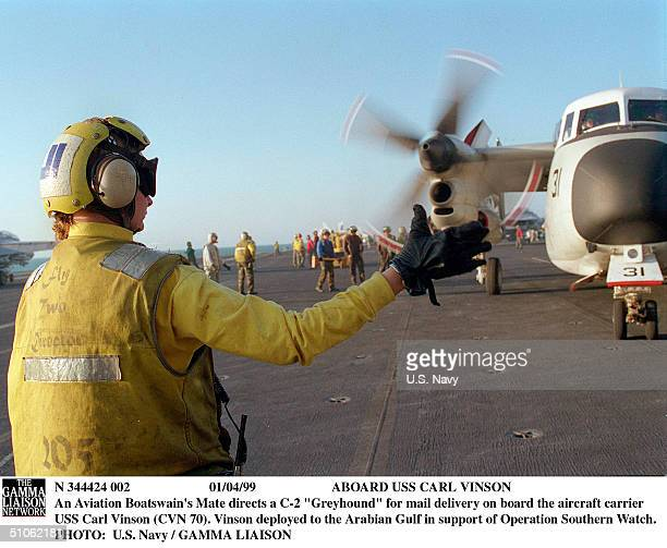 """Aboard USS Carl Vinson An Aviation Boatswain's Mate Directs A C-2 """"Greyhound"""" For Mail Delivery On Board The Aircraft Carrier USS Carl Vinson ...."""
