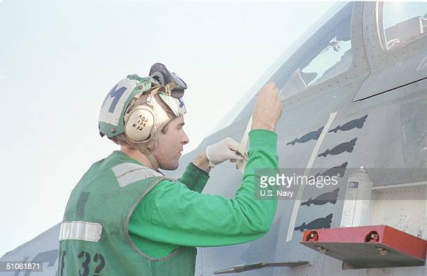 Aboard USS Enterprise A Crewman Of The USS Enterprise Takes Advantage Of A Lull In Activities In Between Air Strikes Against Iraq To Paint Icons Of...