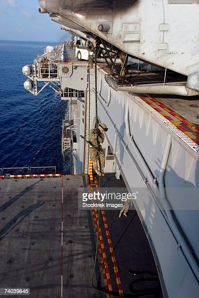 Aboard USS Essex Marines and sailors with Company G fast-rope from the rear of a CH-46E Sea Knight helicopter May 9 which is parked overhanging the edge of the flight deck here.