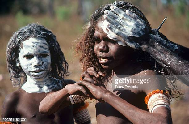 Aborginal man painting white clay on  girl's (6-7) face, close-up, Arnhemland, Australia