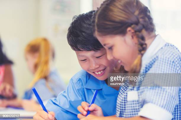 aboriginal and asian students working together. - uniform stock pictures, royalty-free photos & images