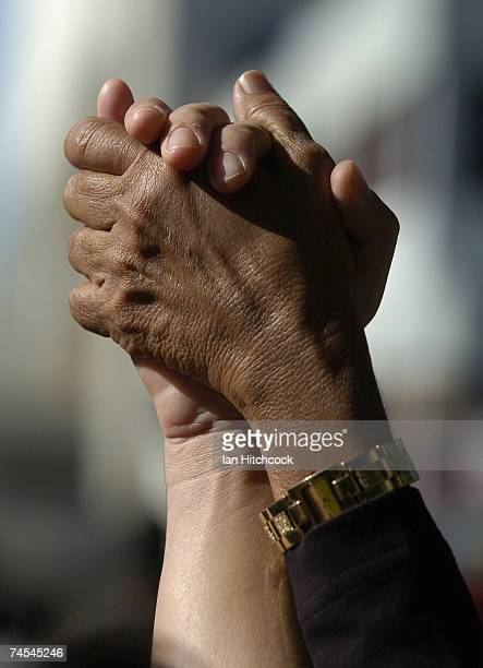 Aboriginal and Caucasian hands are pictured together during prayers outside the Townsville Courthouse June 12 2007 in Townsville Australia Queensland...